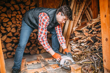 Handsome Man Cuts The Wood With A Circular Saw, Cutting Wood For The Fireplace, Shed With Wood