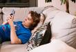 Chłopak młody z telefonem na kanapie. Cyber relaks
