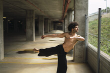 Shallow Focus Of A Curly-haired Topless Man Dancing In A Parking Lot In Spain