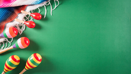 Cinco de Mayo holiday background made from maracas, mexican blanket stripes or poncho serape on green background.