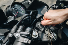 Close Up Of Motorcycle Rider Hand Inserting The Key For Starting The Motorcycle Engine.