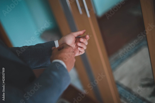 Fotografering Closeup of a man fixing his cufflinks in a dressing room with a blurry backgroun