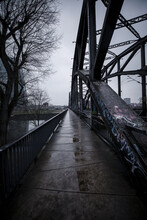 Scenic View Of An Empty Road And Suspension Bridge Under A Gloomy Sky