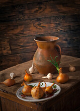 Vintage Ceramic Jug With Garlic And Onions On A Dark Wooden Back