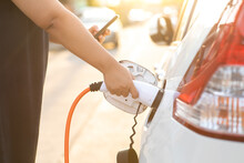 World Environment Day. Save World Save Life Concept. Close Up Woman Hand Holding Electric Car Plug For Recharge Plug In Hybrid Car At Home Or Charging Station.