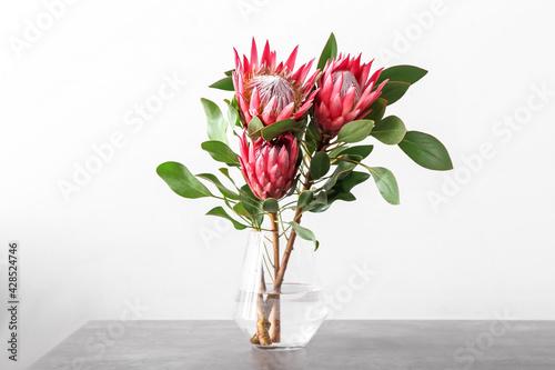Fototapeta Vase with beautiful protea flowers on light background obraz