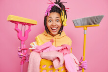Positive Afro American Housewife Smiles Broadly Feels Happy Holds Broom And Mop Stands Near Laundry Basket Isolated Over Pink Background. Cheerful Woman Glad To Finish Cleaning. Keep Your House Clean
