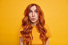 Horizontal Shot Of Impressed Redhead Woman Looks With Great Wonder At Camera Keeps Lips Folded Hears Shocking News Dressed In Casual Outfit Isolated Over Yellow Background. Human Reactions Concept