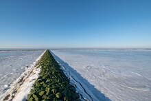 Beautiful View Of A Frozen Lake Surrounded By Stones In The Wintertime Against A Blue Sky