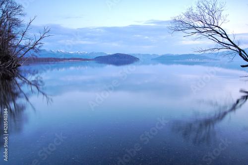 淡い青色の夜明けの湖。 Fotobehang