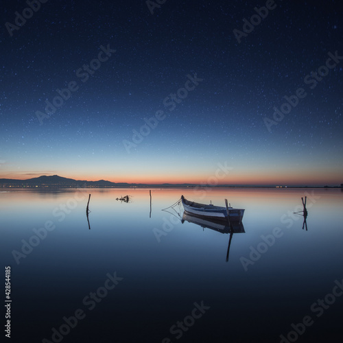Fototapeta Boat on the sea with long exposure under a beautiful starry sky in the evening obraz