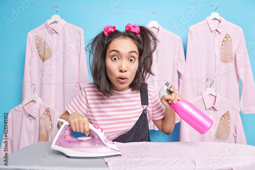Fototapeta Shocked Asian woman with two pony tails holds detergent bottle busy ironing laundry at home wears striped t shirt and overalls poses against blue background haging shirts around