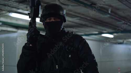 Fotografie, Obraz SWAT soldier posing at camera with assault rifle in urban building