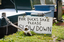 Slow Down Sign Next To Narrow Boat On Grand Union Canal, UK