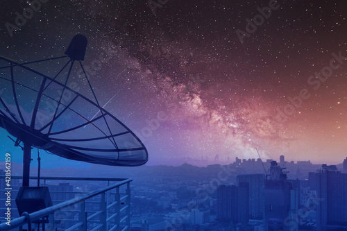 Obraz na plátně Satellite dish at night sky and stars background, View of high rise buildings in