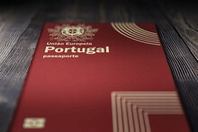 Close-up Of A Portuguese Passport On A Dark Wooden Board, Citizenship By Investment