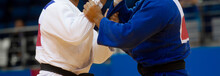 Two Judo Fighters In White And Blue Uniform. Professional Sport Concept