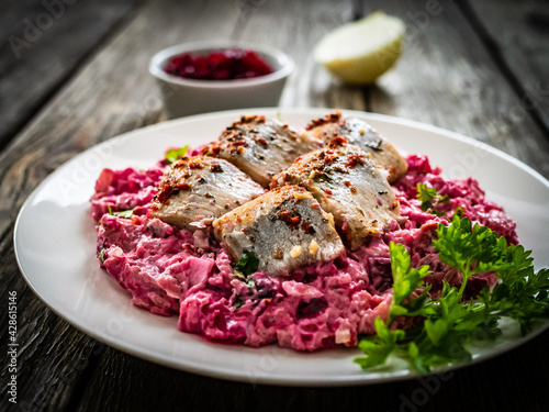 Fototapeta Marinated herring fillets in cream with roast beetroots, pickled cucumber, boiled potatoes, parsley, onion and apple on wooden table  obraz