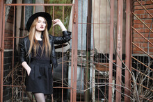 Young Beautiful Girl In A Hat And With A Dark Make-up Outside. Girl In The Gothic Style On The Street. A Girl Walks Down The City Street In A Leather Waistcoat With A Phone.