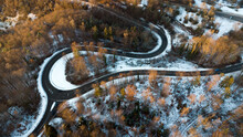 Aerial Shot Of A Winding Crossroad Through The Winter Forest