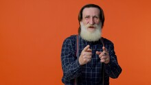 Senior Old Bearded Gray-haired Grandfather Making Playful Silly Facial Expressions And Grimacing, Fooling Around, Pointing At Camera. Mature Funny Man Isolated On Orange Background