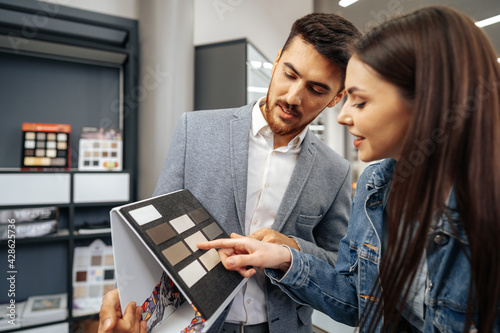 Salesman shows color swatches to lady customer for new kitchen furniture - fototapety na wymiar