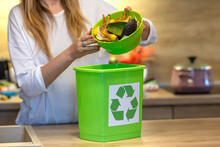 Woman Recycling Organic Kitchen Waste By Composting In Green Container During Preparation Of Meal. A Young Girl Throws Vegetable Cuttings In A Compost Bucket. Plastic Compost Bucket.