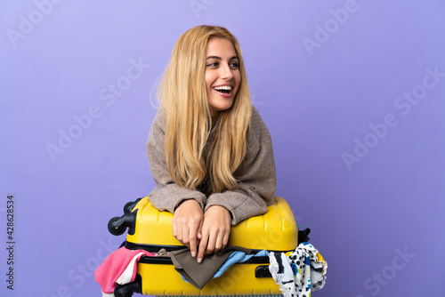 Young Uruguayan blonde woman with a suitcase full of clothes over isolated purple wall