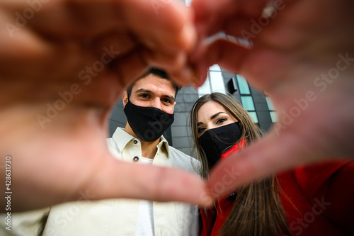 Fototapeta Couple wearing masks and making the sign of a heart, covid and coronavirus concept obraz