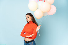 Young Woman Catching Many Balloons Isolated On Blue Background Laughing