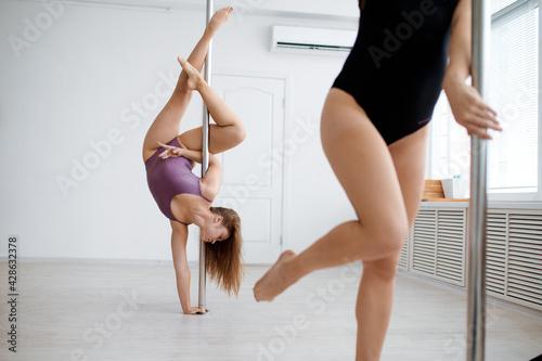 Two sexy women practice pole dancing - fototapety na wymiar