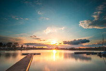 Sunset At The Lake, A Beautiful Summer Evening By The Water With Pale In The Sun, Reflection In The Water, A Natural Landscape
