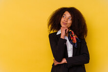 Young African American Air Hostess Isolated On Yellow Background Looking Sideways With Doubtful And Skeptical Expression.