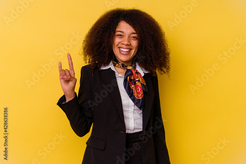 Billede på lærred Young African American air hostess isolated on yellow background showing a horns gesture as a revolution concept