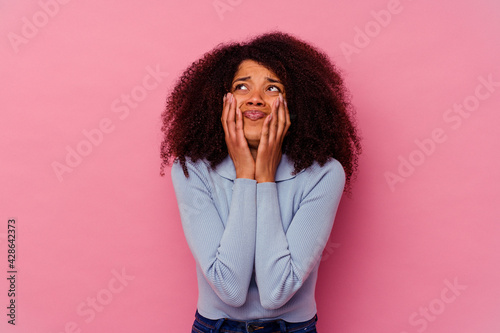 Fotografiet Young african american woman isolated on pink background whining and crying disconsolately