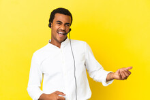 African American Telemarketer Man Working With A Headset Over Isolated Yellow Background Making Guitar Gesture