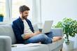 Leinwandbild Motiv Young man study at home sitting on sofa using laptop