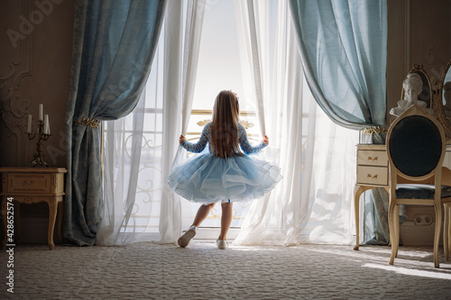 Canvas Print Back view of little girl in blue dance dress standing by the window, opening curtains in luxury apartment bedroom and looking out at the sea