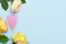 Pink Menstrual Cup Lies On Blue Background With Yellow Roses Flowers. Copy Space.
