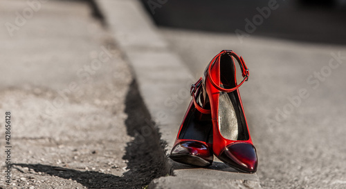 Fotografia, Obraz Pair of red high heels on asphalt with the sunlight falling on them