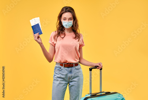 Pretty girl in casual clothes with suitcase, passport, tickets and medical protective mask isolated on yellow background. Tourism, travel, recreation concept. - fototapety na wymiar