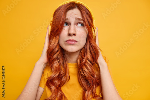 Fototapeta Displeased melancholic ginger teenage girl keeps hands on stereo headphones thinks about somethig sad while listening music dressed casually looks aside sadly isolated over yellow background obraz