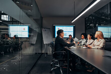 Work Team. A Group Of Successful Business People Work Hard In The Conference Room Of A Large Spacious Office. In The Room There Is A Monitor With Graphs And A Flipchart With A Plan.