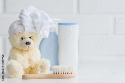 Fotografia Baby bath accessories, baby care, a yellow bear with a towel on its head, a brush and bottles of shampoo