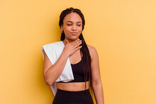 Young Sport African American Woman Holding A Towel Isolated On Yellow Background Suffers Pain In Throat Due A Virus Or Infection.