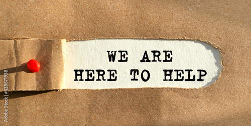 Fotografia The text WE ARE HERE TO HELP appears behind the torn paper
