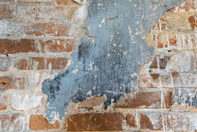 An Old Wall Of Red Brick With Remnants Of Plaster And Cracked Paint