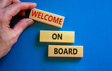 Welcome On Board Symbol. Wooden Blocks With Words 'Welcome On Board'. Beautiful Blue Background, Businessman Hand. Business, Welcome On Board Concept, Copy Space.