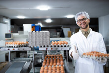 Portrait Of Food Factory Worker With Hairnet And Hygienic Gloves Holding Eggs By Industrial Transporting And Packing Machine In Food Processing Plant.