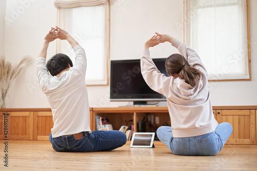 自宅のリビングでストレッチをするアジア人の夫婦